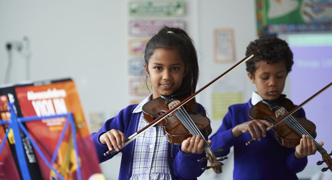 two children playing violin