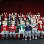 big group of young children wearing Christmas jumpers