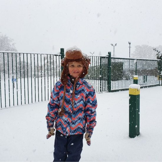 child standing in the snow wearing a hat, coat and gloves
