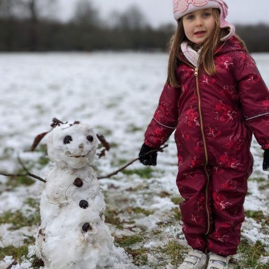 young girl standing next to a small snowman