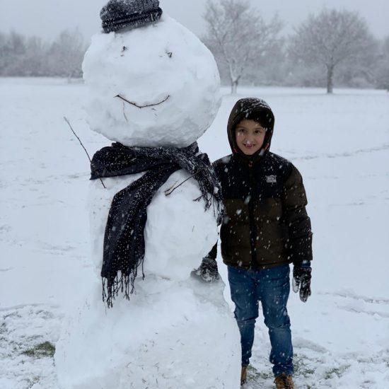 Child next to a snowman