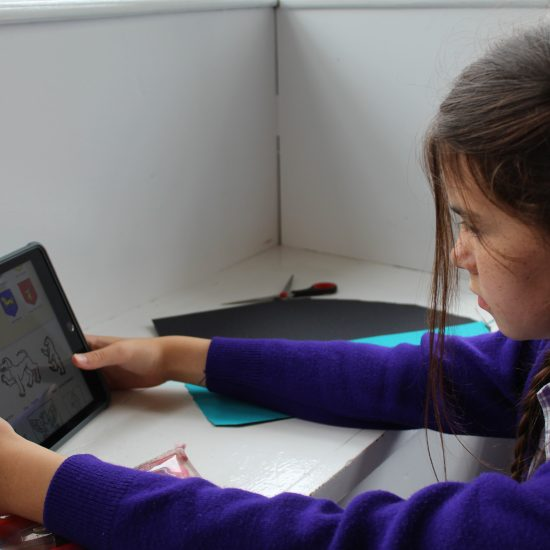A child using a tablet to look at reference images for their crafts project in class