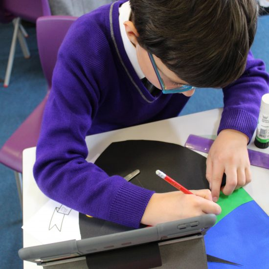 A child in purple uniform in an arts and crafts lesson